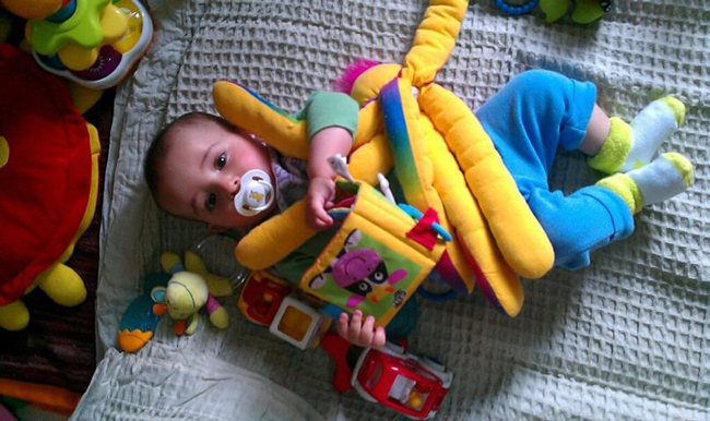 baby lying with his toys