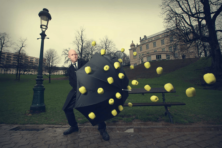 Man with umbrella and flying green apples