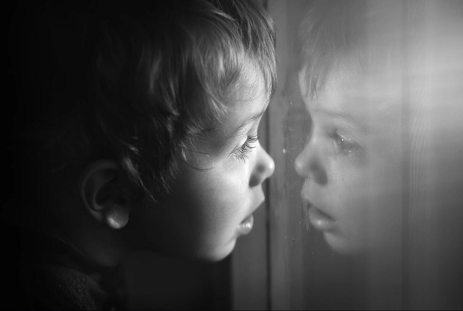 black and white picture of child looking himself in a glass by wix phtoographer kuzilova