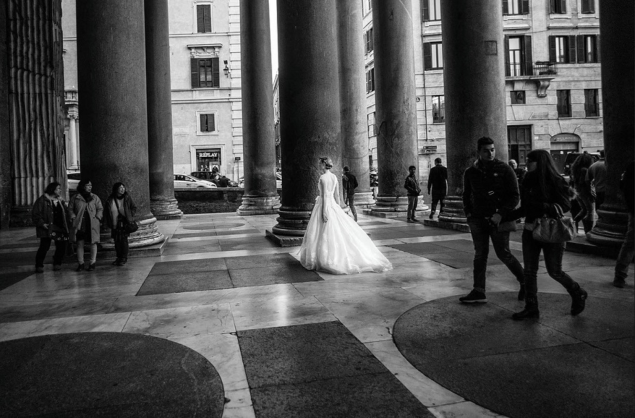 black and white picture of a bride with a wedding dress on the porch of the church by wix photographer Roberto Vamos