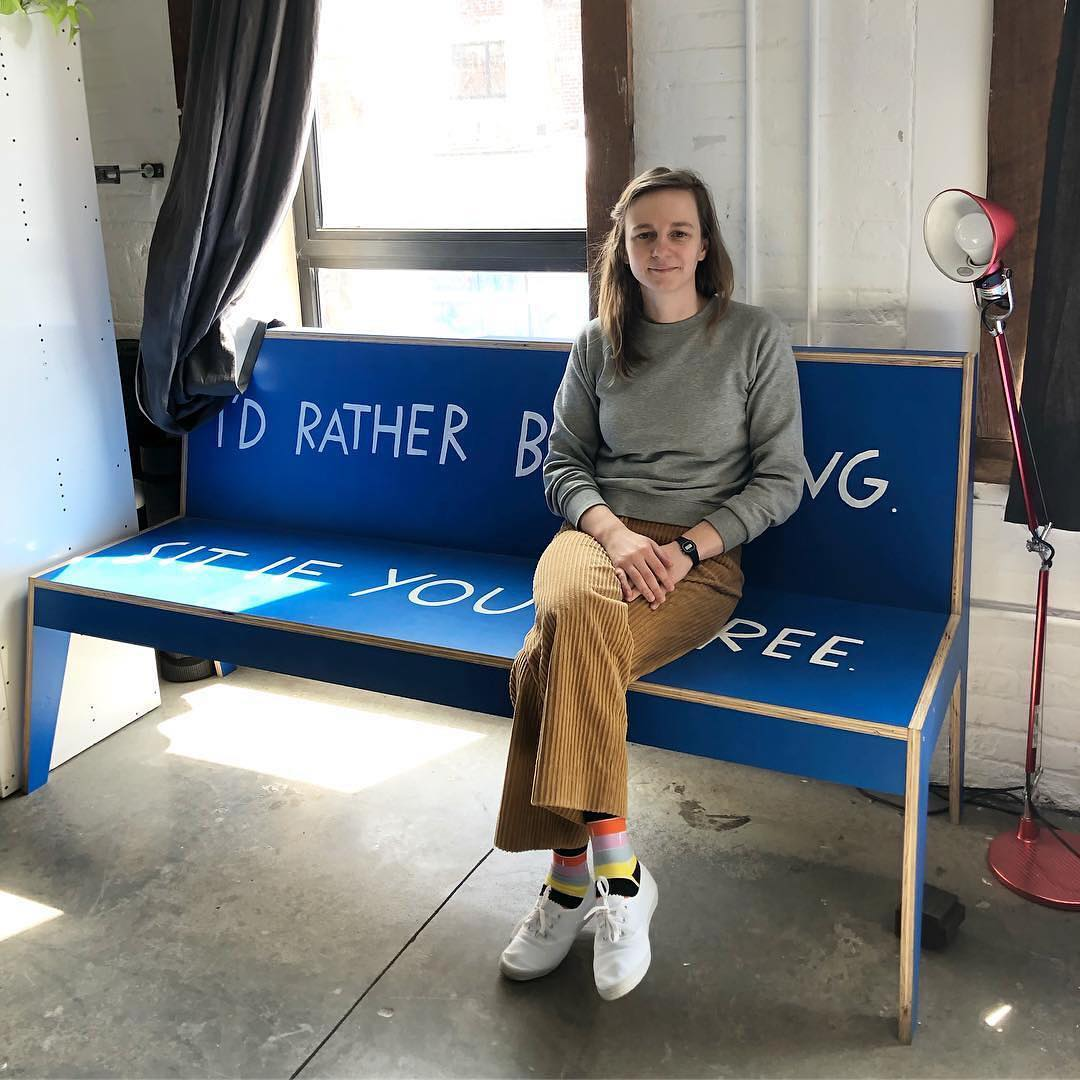 Shannon Finnegan sitting on a bench that reads, I'd Rather be Sitting, Sit if You Agree.