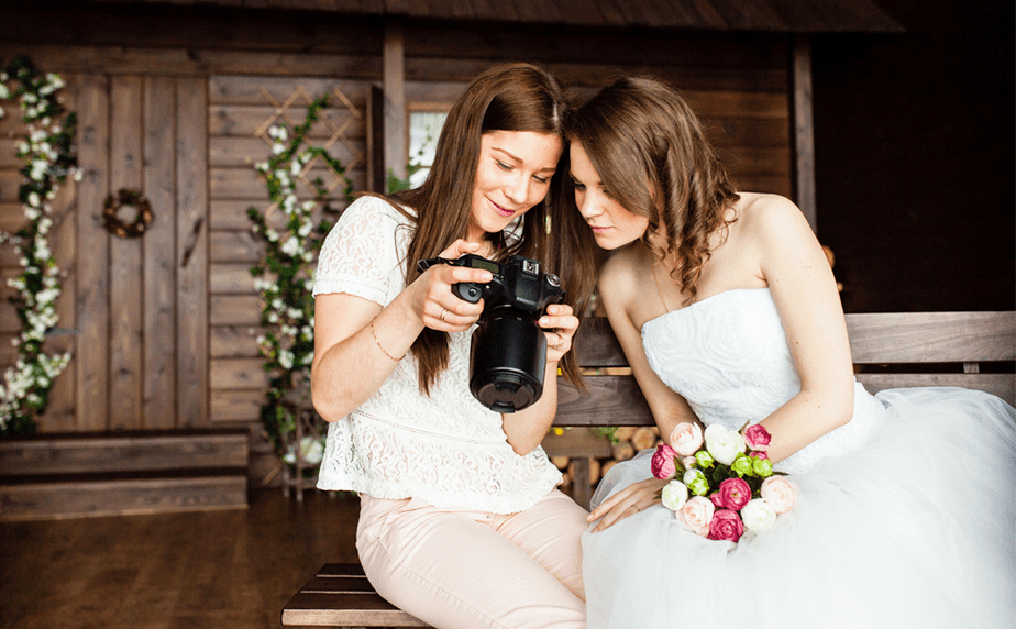 Weddingphotographer showing photos to the bride