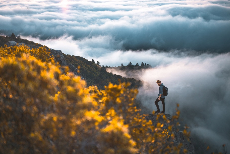 Man climbing a mountain surrounded by clouds by Wix photographer Nikk La
