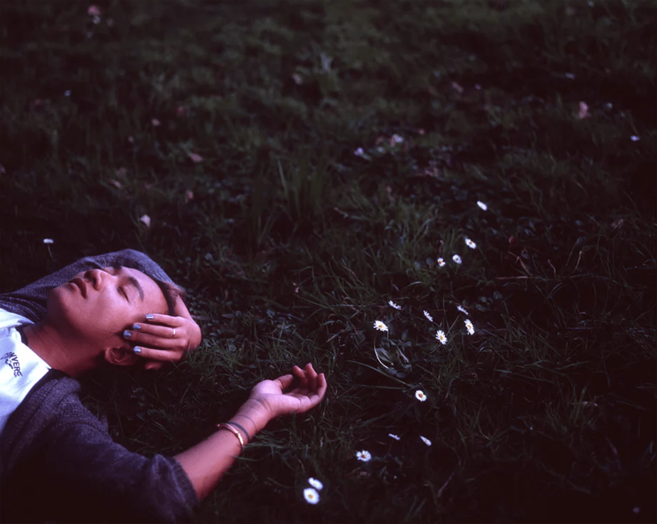 Man daydreaming on grass with flowers