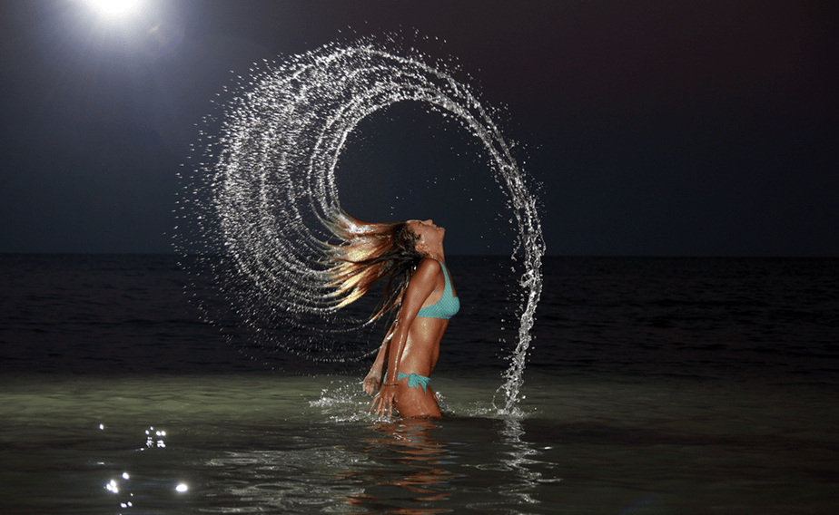 Girl with long hair splashing water.