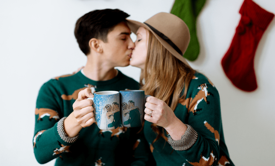 couple kissing with two matching mugs