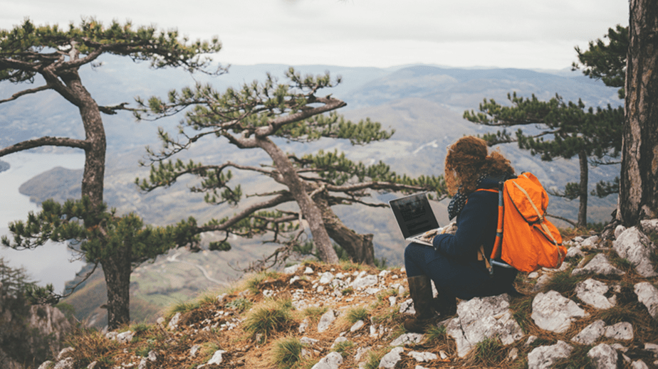 Woman with laptop and backpack facing a beautiful landscape.