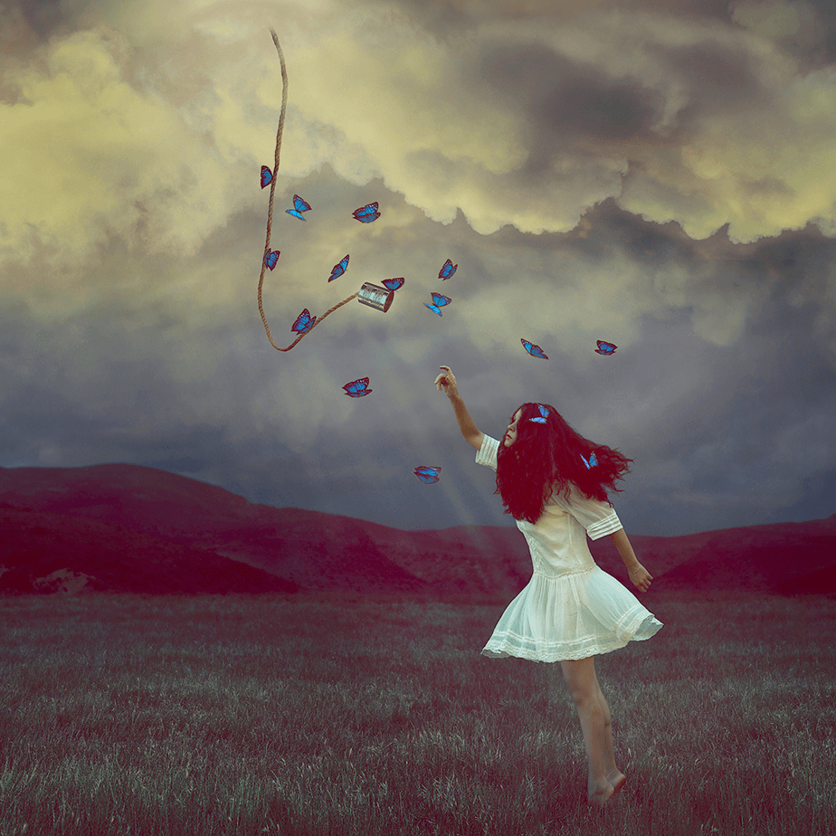 woman reaching out to the sky with butterflies