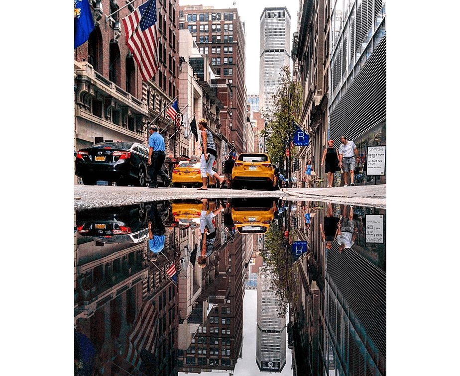 Reflection photo of a street in New York City mirrored in a puddle