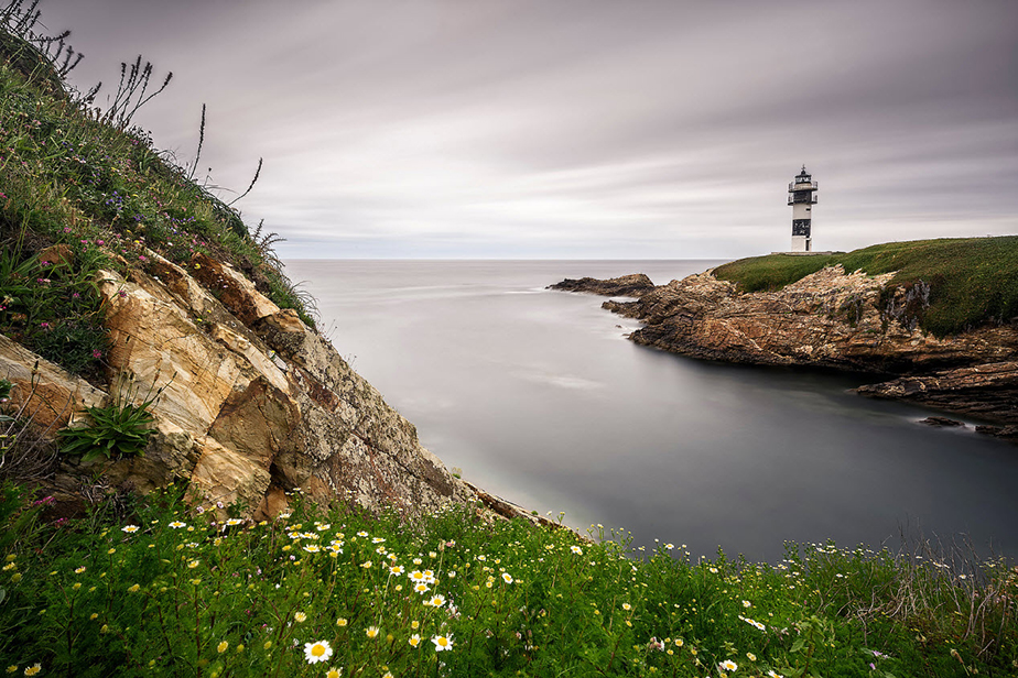 the sea reaches the cliffs and the lighthouse