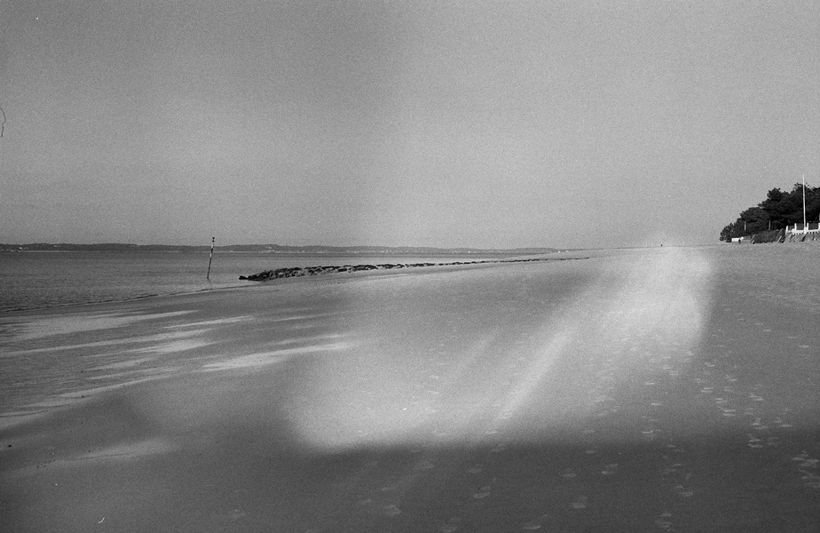 black and white photo of an empty beach with light leak