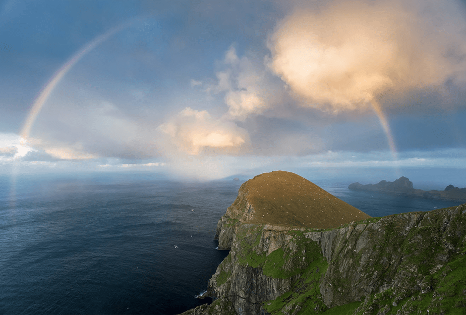 a full rainbow appears over the sea at the end of a mountain cliff