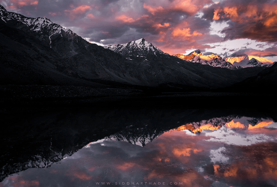 sunset over snowy mountains surrounding a lake