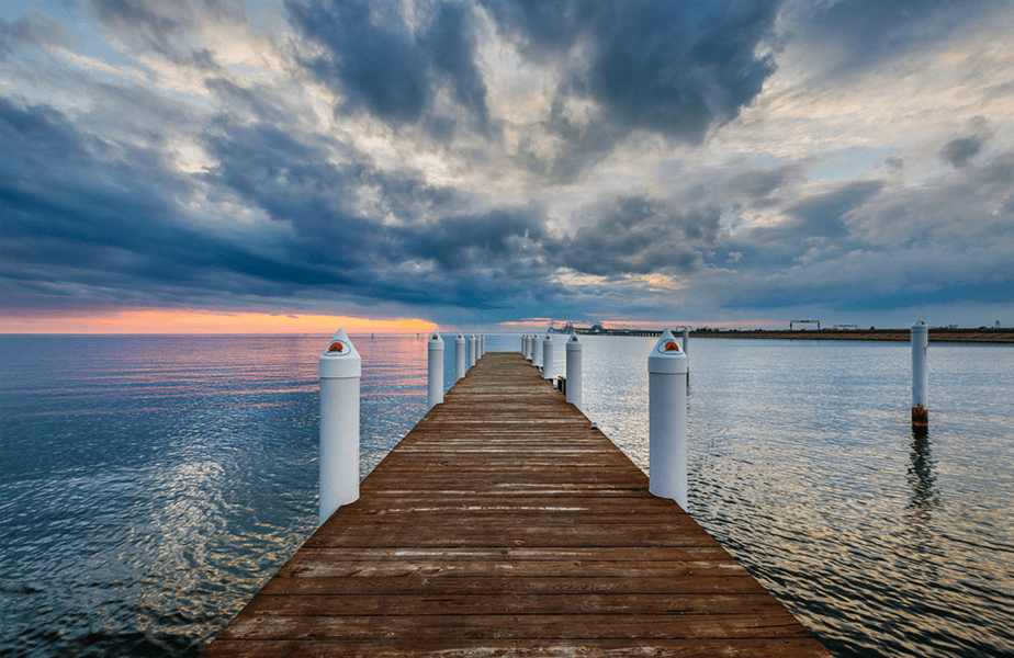 pier leading into the sea water during sunset
