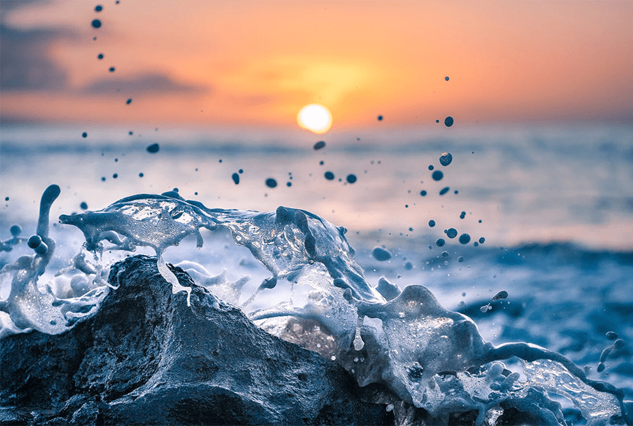 sea wave splashing on a rock as the sunset falls on the horizon