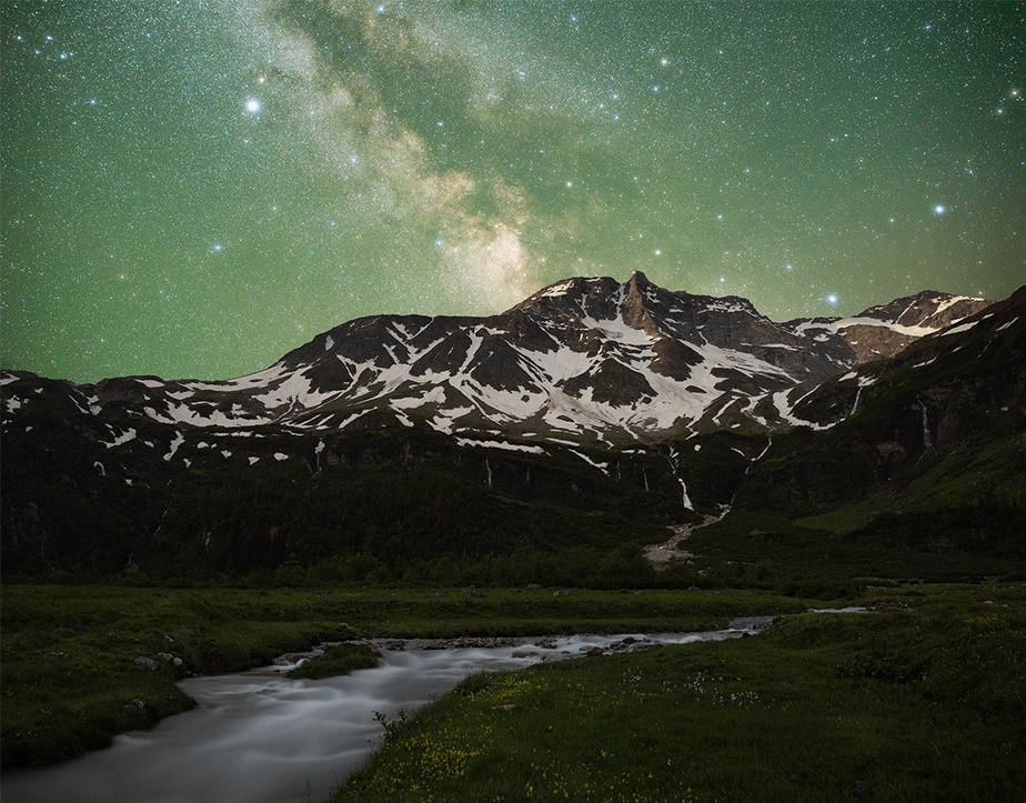 milky way over the snowed mountains with a river on the foreground