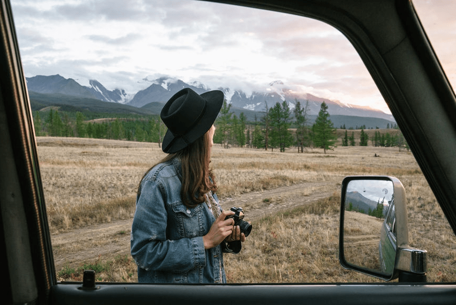 girl with a hat and a camera stands outside her car while on the mountains