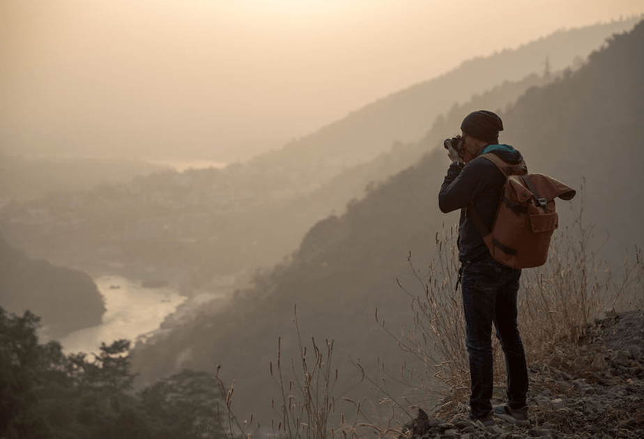 photographer standing on a mountain cliff taking pictures