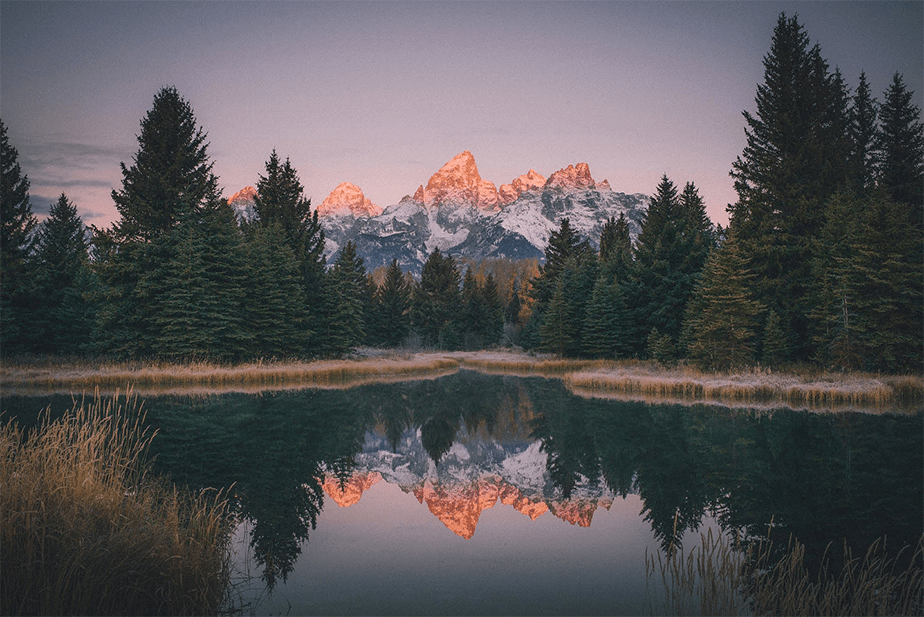 sunset mountains and trees reflected on a lake