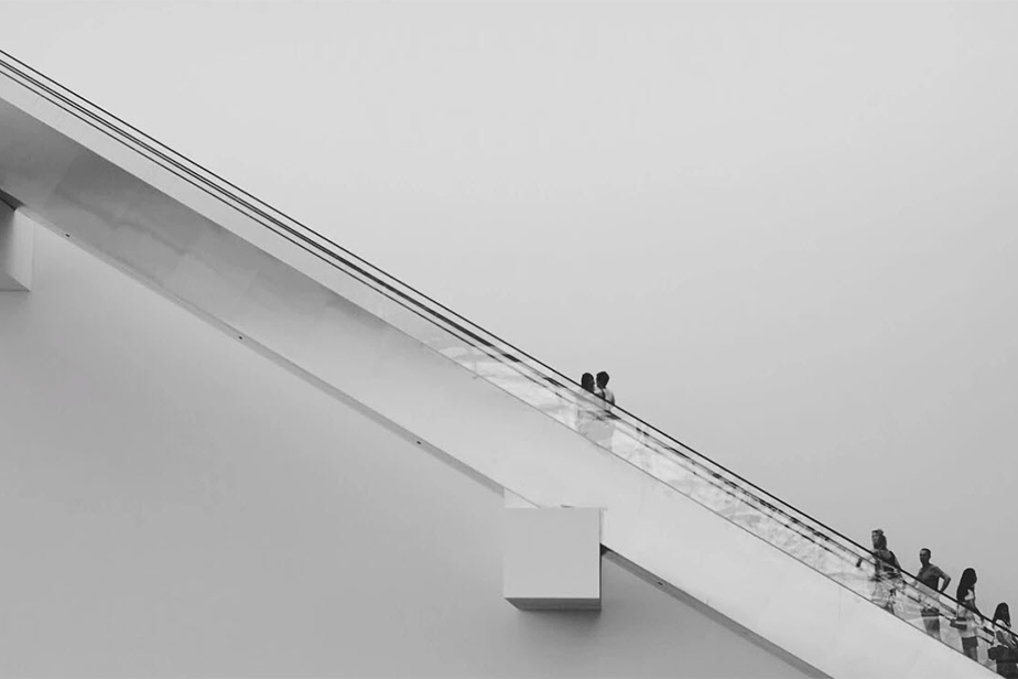 minimalist monochromatic urban shot with people going up the stairs
