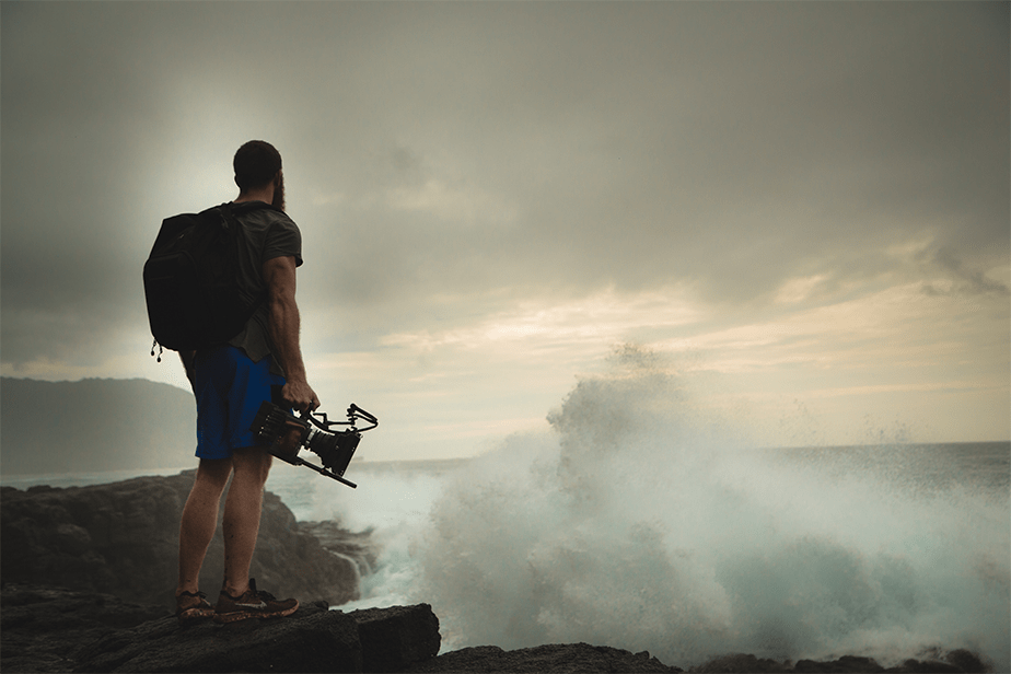 cameraman standing on rocks next to the sea waves