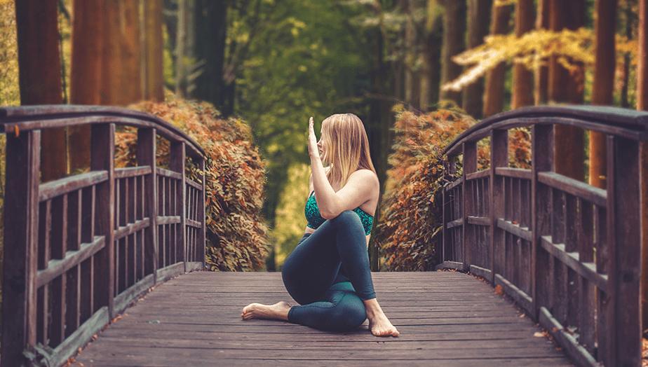 yoga pose on forest bridge