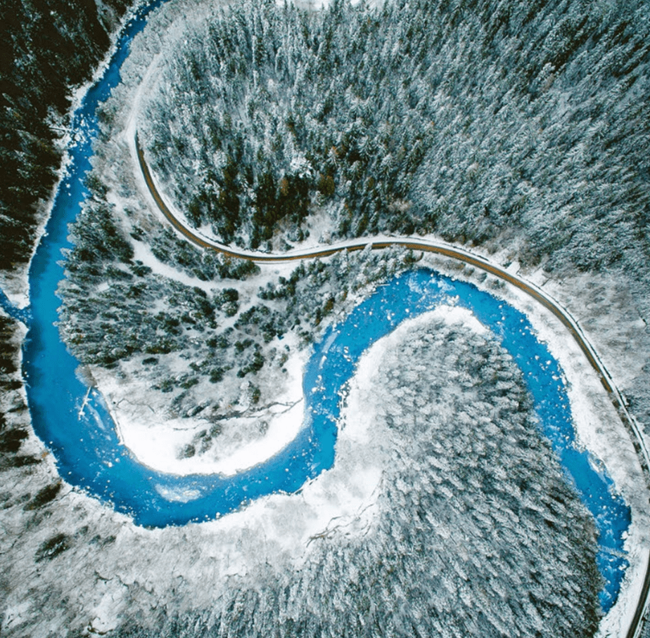 dron photo of snowed forest and blue river