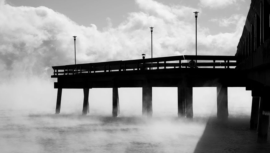 black and white photo of pier and sea at winter